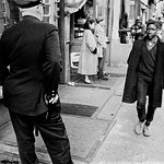 USA. NYC. 1960. Policeman watches a black teenager in Harlem.